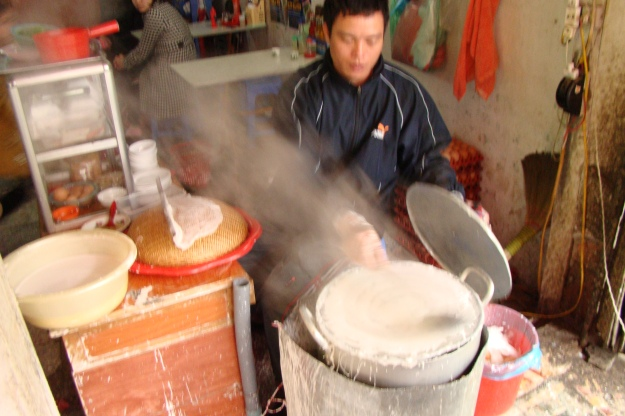 They take a rice flour and water mixture, spread it on a hot round sheet, cover with a lid and let it steam for a short while.