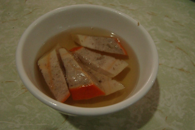 The dish is served with a clear fish sauce broth and pieces of pork.